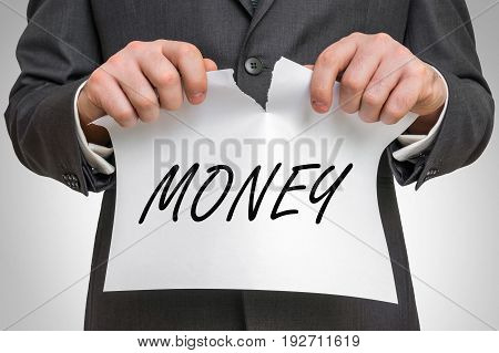 Businessman Tearing Paper With Money Word