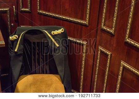 Close up chair of a hotel bellboy with jacket hanging on it