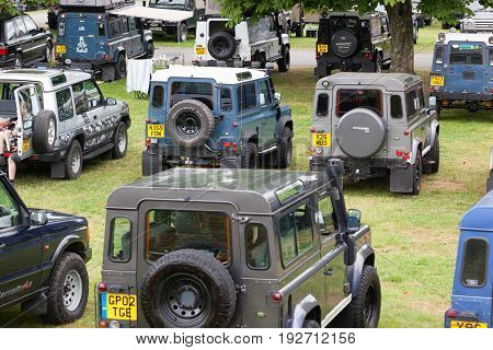 BEAULIEU HAMPSHIRE UNITED KINGDOM - JUNE 25 2017 Land Rover day with many varieties of Land Rovers including the types Defender Range Rover and Discovery. Parked on a field with trees.