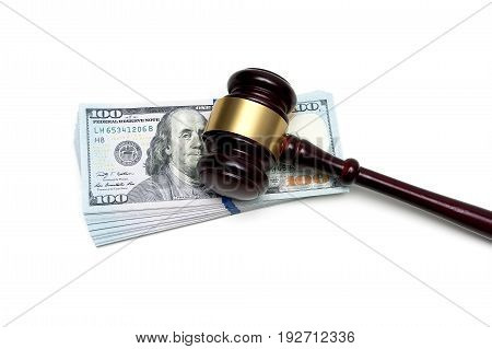 gavel lying on a big stack of money isolated on white background. horizontal photo.