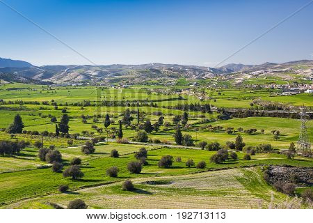 View of beautiful landscape with fresh green meadows and mountain tops in the background on a sunny day with blue sky and clouds in springtime