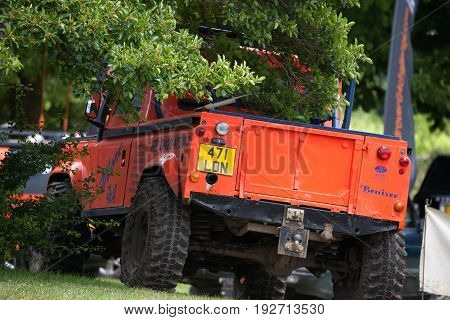 BEAULIEU HAMPSHIRE UNITED KINGDOM - JUNE 25 2017 Land Rover day with many varieties of Land Rovers including this Defender in an orange color parked under a tree.