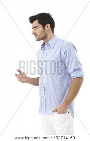 Young man turning right, talking, gesturing, standing with left hand in pocket.