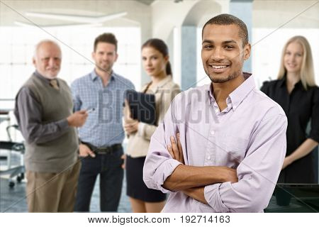 Confident young businessman smiling happy with a team behind.