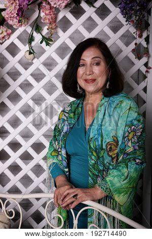 Mature asian woman standing in flower garden a luxurious dress.