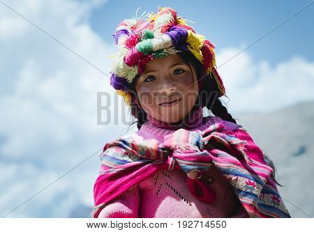 Smiling peruvian girl dressed in colourful traditional handmade outfit. October 21 2012 - Patachancha, Cuzco, Peru