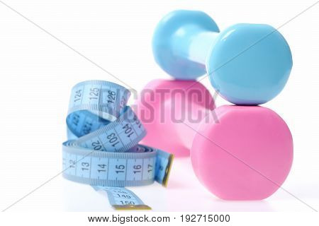 Dumbbells In Cyan And Pink Colors Near Blue Measuring Tape