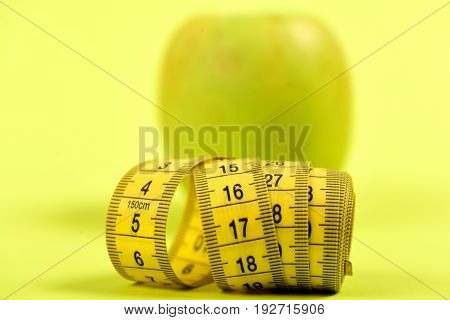 Tape For Measurement In Yellow Colour With Green Apple Behind