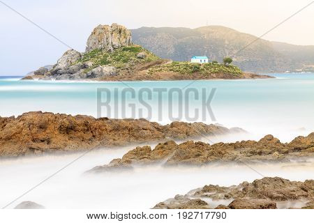 Rocks and small island Kastri in Kos Greece. Long exposure of photography idyllic scene.