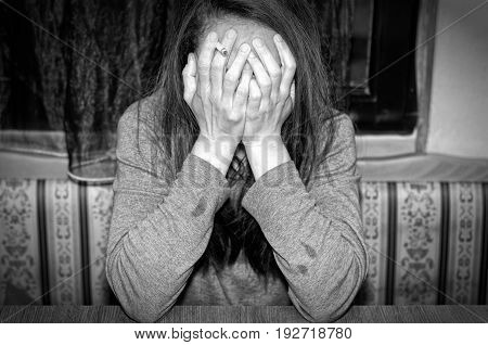 Depression. Depressed woman with cigarette cover her face with her hands. Black and white.