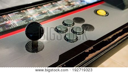 Detail of black joystick gray and yellow buttons on vintage arcade game machine