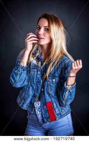 girl In a jeans jacket on a black background