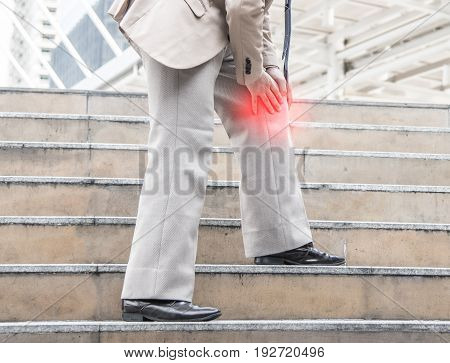 Businessman Suffering from knee Pain on stair, pain and injury concept.