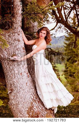 Young bride standing on a tree with her white shoulder-free dress