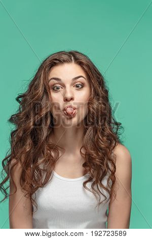 The young Funny dumb woman's portrait with happy emotions on studio background
