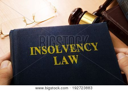 Hands holding insolvency law. Company bankruptcy concept.