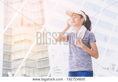 beautiful asian sport girl wiping sweat with towel in city, sport people concept.