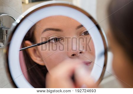 Woman putting mascara in ring light round makeup mirror at home bathroom morning routine. Beautiful Asian girl getting ready applying eye make-up with brush. Closeup on eye in reflection.