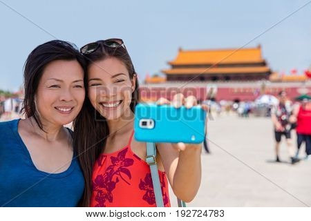 Mother daughter tourists taking travel holiday selfie at Tiananmen Square Beijing, China, Asia. Smiling women taking pictures together at famous Beijing landmark.