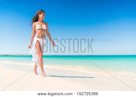 Luxury beach travel vacation swimwear woman relaxing walking on white sand in beachwear cover-up