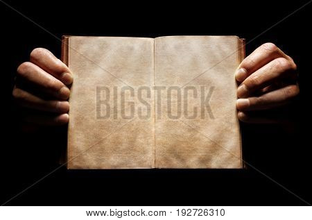 Hands holding an open empty book background in the dark with copy space