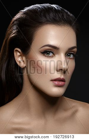 Beautiful young woman with cat eye liner make up. Beauty shot on black background. Copy space.
