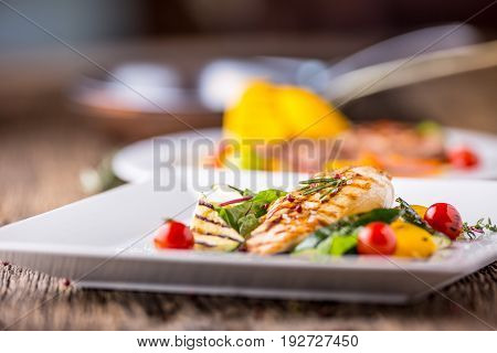 Grill chicken breast. Grilled vegetables with chicken breast. Grilled chicken with vegetables on oak table.
