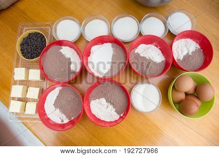 Cookery Set Of Colorful Bowls With Chocolate Drops, Flour, Cocoa Powder, Sugar, Eggs And Blocks Of B