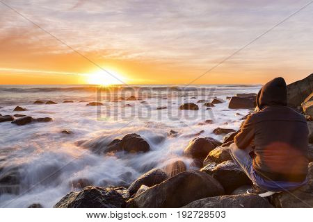 Person sitting on rocks watching sunrise coming over the ocean horizon, with ocean tide washing in over rocks in the foreground.