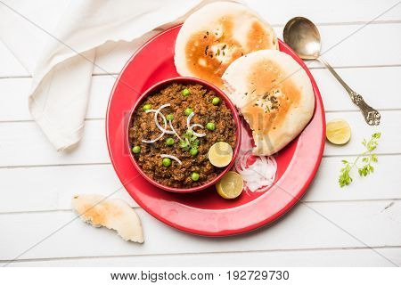 Indian Masala Kheema Pav or khima or Dry Spicy Minced Meat usually served with indian flat bread called kulcha/roti/chapati, garnished with green peas. Selective focus