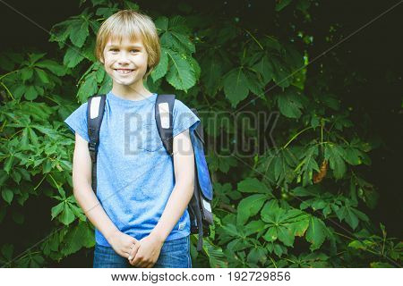 Smiling schoolboy with a backpack going to school. Education, back to school, people concept