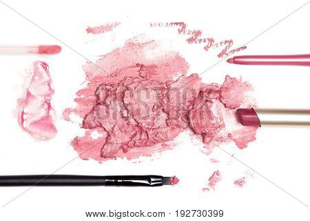 Lip liner, lipstick tube, smeared lipstick, lip gloss pink color with makeup brushes on white background