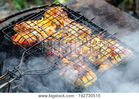 Chicken shashlik being roasted over charcoal on grill