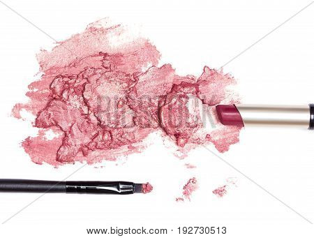 Lipstick tube with smeared lipstick wine color and makeup brush on white background