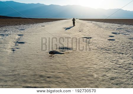 Man Walking on Salt Flats at Badwater Basin in Death valley National Park