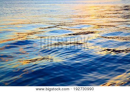 Colorful sea water surface at sundown - abstract background
