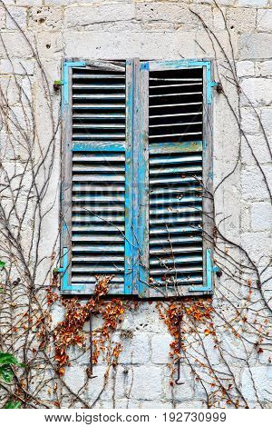 Old house window with closed shutters