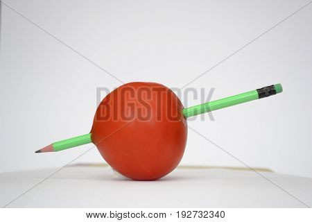 The word can kill - Tomato stabbed with a pencil, just like a heart with an arrow