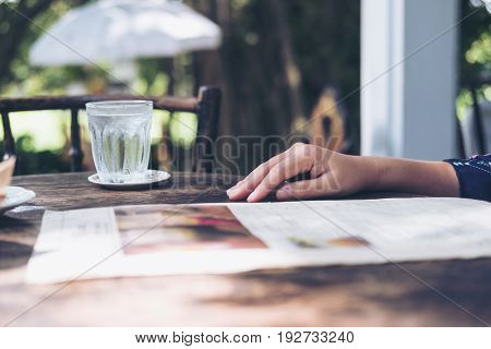 A woman sitting and reading menu on vintage wooden table in restaurant