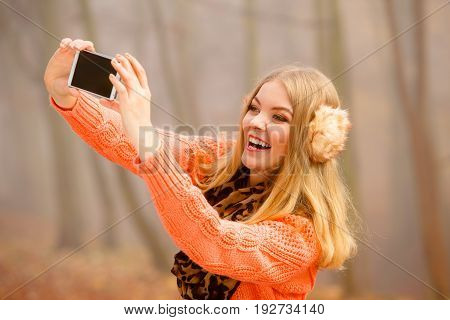 Technology internet and happiness concept. Woman in earmuffs content girl taking self picture selfie with smartphone camera while walking outdoors in autumn park in foggy day
