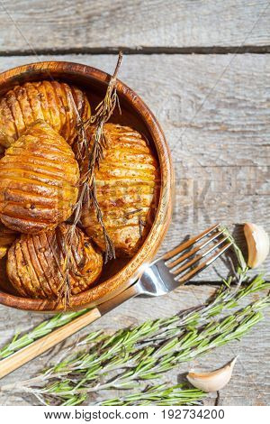 Baked potatoes with rosemary in a wooden bowl.