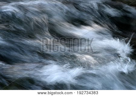 Turbulent water flowing over the rocks in the creek and sparkling