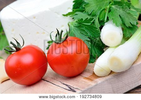 Vegetables with cheese on wooden table closeup