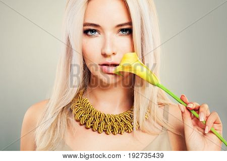 Beautiful Blonde Woman with Healthy Blond Hair Makeup and Yellow Flowers. Cute Girl Fashion Model with Blonde Hairstyle
