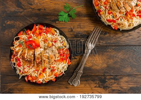 Grilled chicken breast and pasta with tomatoes red bell peppers and parsley on the black plates on the wooden rustic table top view.