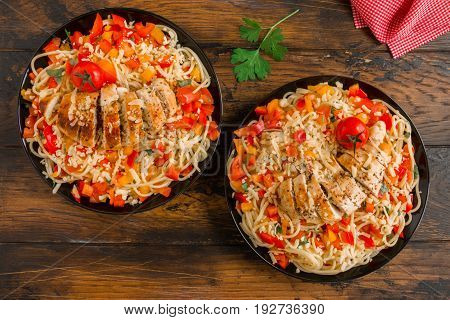Baked boneless skinless chicken breasts and pasta salad with fresh vegetables on the black plates on the wooden rustic table top view.