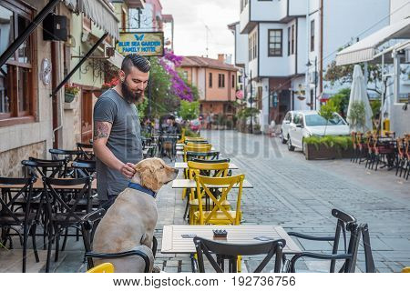 31 May 2017. A man with his dog standing near a cafe on the street of an old sity in Antalya. Turkey, quarter Kaleici.
