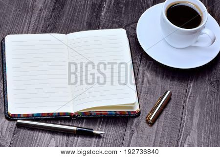 Empty notebook with fountain pen and coffee on table