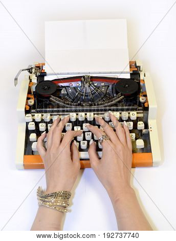 Women's hands on the keyboard of the old typewriter