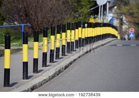 Black and yellow protective poles on the sidewalk along a steep street